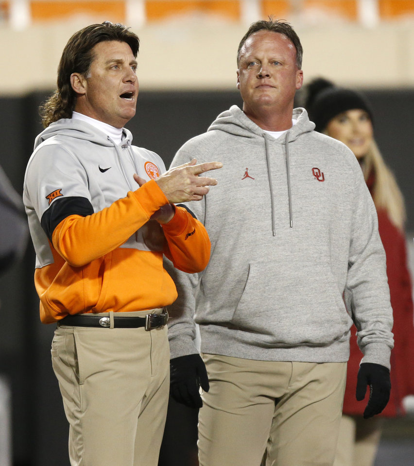 Photo - Brothers Mike Gundy, OSU head coach, left, and Cale Gundy, OU assistant coach,  talk before the Bedlam college football game between the Oklahoma State Cowboys (OSU) and Oklahoma Sooners (OU) at Boone Pickens Stadium in Stillwater, Okla., Saturday, Nov. 30, 2019. [Nate Billings/The Oklahoman]