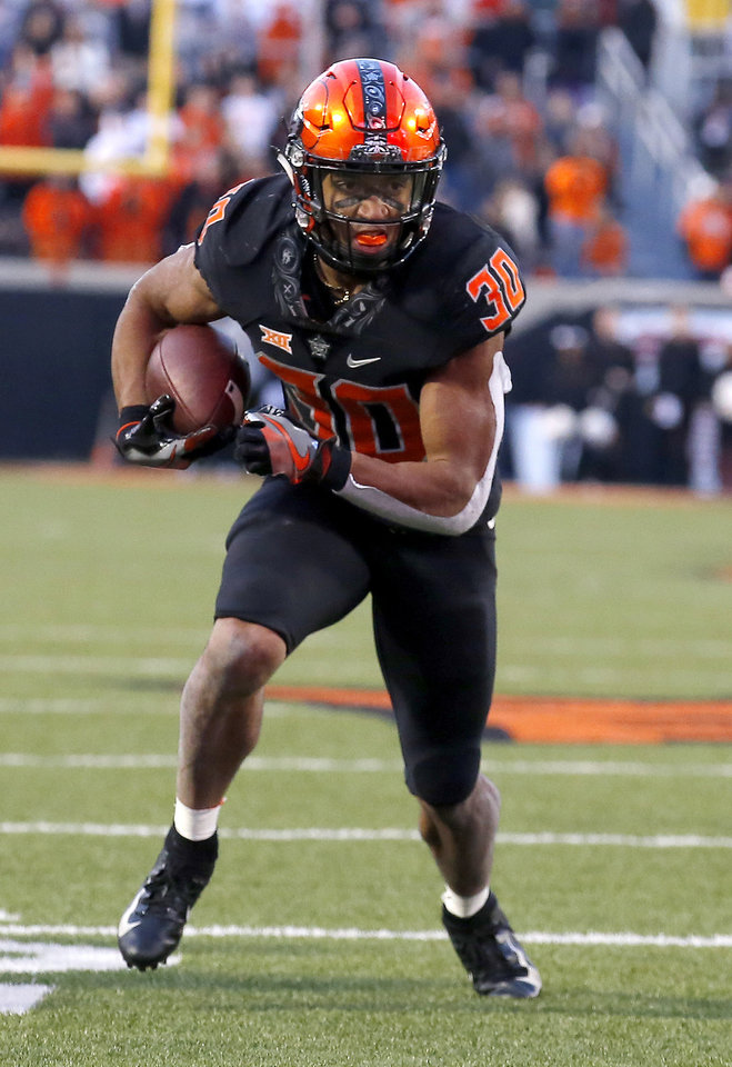 Photo - Oklahoma State's Chuba Hubbard (30) rushes in the fourth quarter during a college football game between the Oklahoma State Cowboys (OSU) and the West Virginia at Boone Pickens Stadium in Stillwater, Okla., Saturday, Nov. 17, 2018. OSU won 45-41.Photo by Sarah Phipps, The Oklahoman