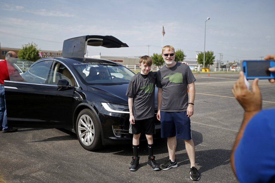 Photo -  Shawn McDown and his son, William, 12, pose for a photo in front of a Tesla Model X at OG&E's Electric Vehicle Ride and Drive event.