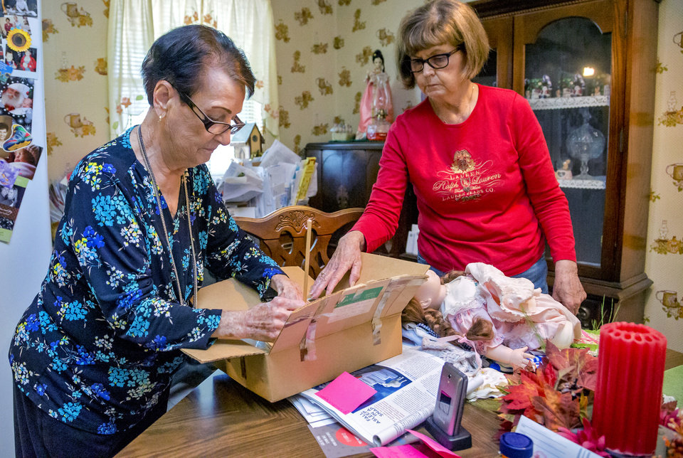 Photo -  Imogene McDowell and Sandi Burrow sort through the supplies McDowell uses to repair and mend the dolls at her home in Mustang. [Photo by Chris Landsberger, The Oklahoman]