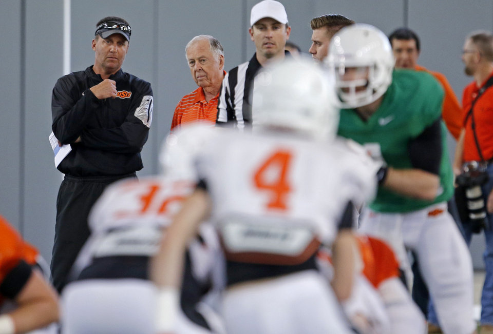 Photo - Boone Pickens, left, talks with Oklahoma State head football coach Mike Gundy during a practice in Stillwater, Okla., Friday, April 10, 2015. Photo by Bryan Terry, The Oklahoman