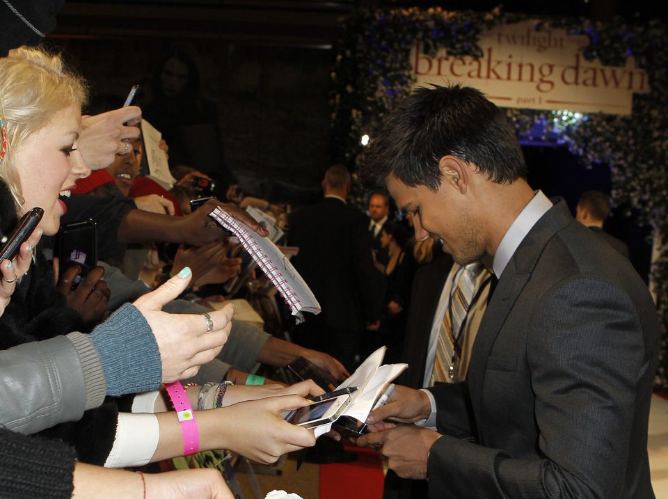Photo - US actor Taylor Lautner signs autographs as he arrives at the UK film premiere of 'Twilight Breaking Dawn Part 1' at Westfield Stratford in east London, Wednesday, Nov. 16, 2011. (AP Photo/Joel Ryan) ORG XMIT: LENT111