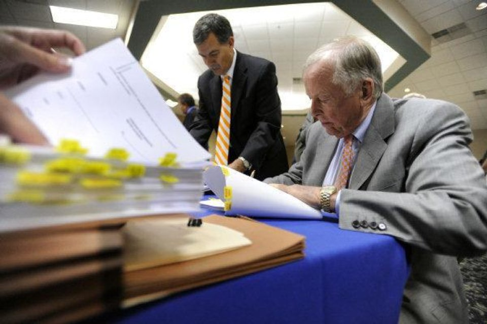 Photo - Attorney Marty Jones, left, helps T. Boone Pickens, of Mesa Water Inc., sign a contract giving Mesa water rights to Canadian River Municipal Water Authority during a special meeting of the CRMWA Board of Directors at the Plainview Country Club Thursday, June 23, 2011, in Plainview, Texas. (AP Photo/The Amarillo Globe News, Stephen Spillman)  ORG XMIT: TXAMA102