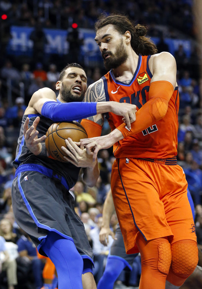 Photo - Oklahoma City's Steven Adams (12), right, and Dallas' Salah Mejri (50) fight for the ball in the second quarter during an NBA basketball game between the Dallas Mavericks and the Oklahoma City Thunder at Chesapeake Energy Arena in Oklahoma City, Sunday, March 31, 2019. Photo by Nate Billings, The Oklahoman