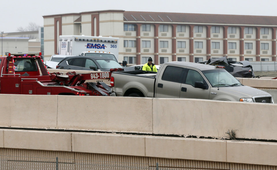 Photo - Wreckers remove vehicles involved in an accident on the entrance ramp to westbound I-44 near NW 63rd and I-235 during freezing rain in Oklahoma City, Wednesday, Feb. 27, 2019. by Nate Billings, The Oklahoman