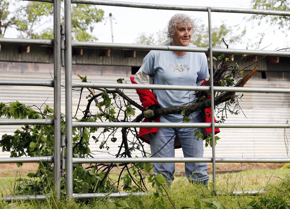 Photo - Mary Flueckiger removes tree limbs from her property damaged by Wednesday's storms on Thursday, May 3, 2018 in Purcell, Okla..  She lost several outbuildings and trees but her horses escaped uninjured.   Photo by Steve Sisney, The Oklahoman