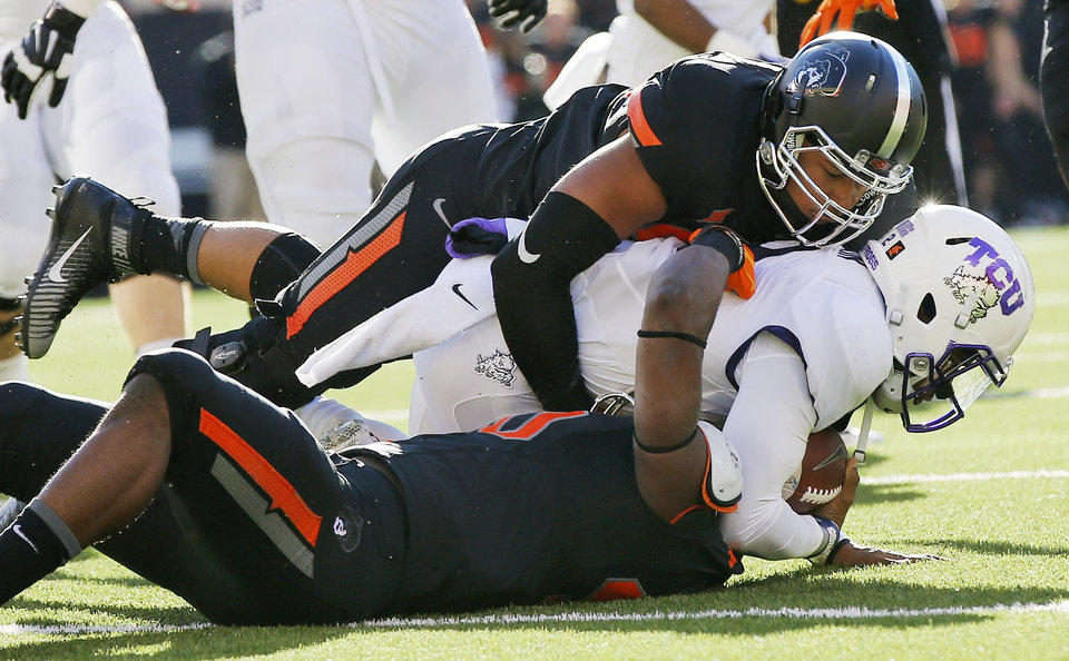Photo - Oklahoma State's Devante Averette (40), bottom, and Jordan Brailford (94) bring down TCU's Trevone Boykin (2) for a loss during the college football game between the Oklahoma State Cowboys (OSU) and TCU Horned Frogs at Boone Pickens Stadium in Stillwater, Okla., Saturday, Nov. 7, 2015. OSU won 49-29. Photo by Nate Billings, The Oklahoman
