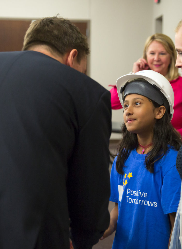 Photo -  Mayah, a student at Positive Tomorrows, shakes hands with fundraiser Todd Lechtenberger after a ceremony for a new facility. The school caters to homeless children. [Photo by Anya Magnuson, The Oklahoman]