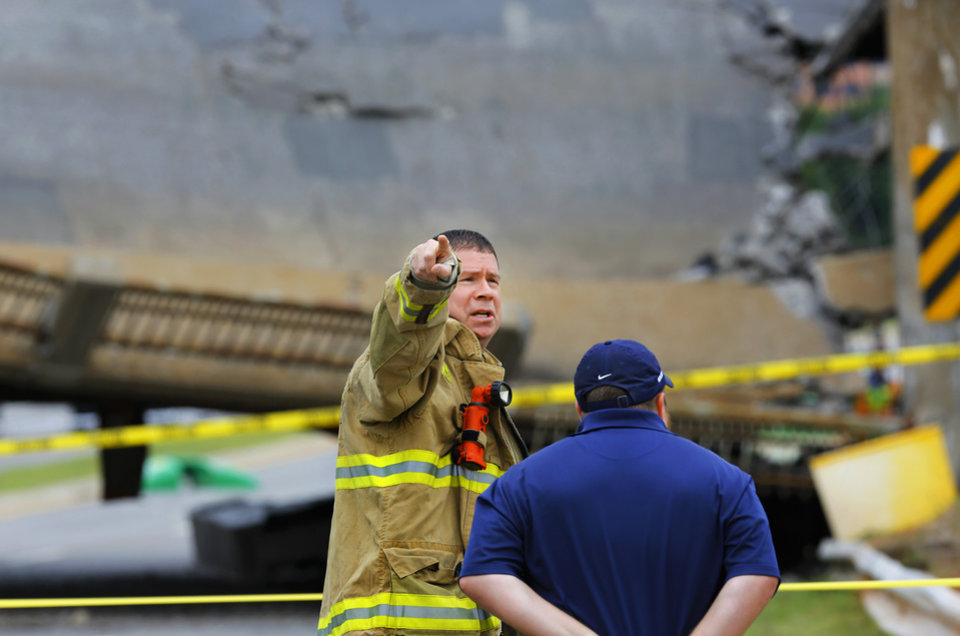 Photo - A section of the May Ave. bridge above the Northwest Expressway collapsed when  it was hit by a truck Thursday afternoon, in  Oklahoma City. No injuries were reported. An Oklahoma City firefighter instructs bystanders to move farther back from the scene of the collapse.  Photo by Jim Beckel, The Oklahoman.