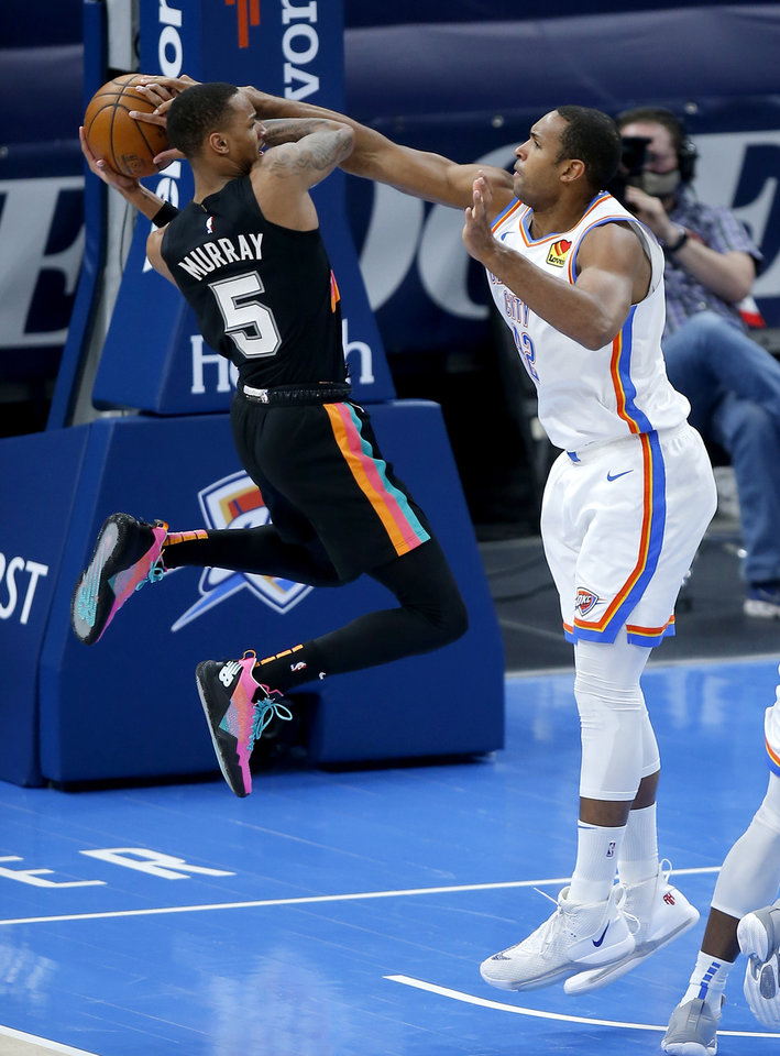 Photo - Oklahoma City's Al Horford (42) forces a jump ball with San Antonio's Dejounte Murray (5) of the NBA basketball game between the Oklahoma City Thunder and the San San Antonio Spurs at the Chesapeake Energy Arena, Wednesday, Feb. 24, 2021. [Sarah Phipps/The Oklahoman]