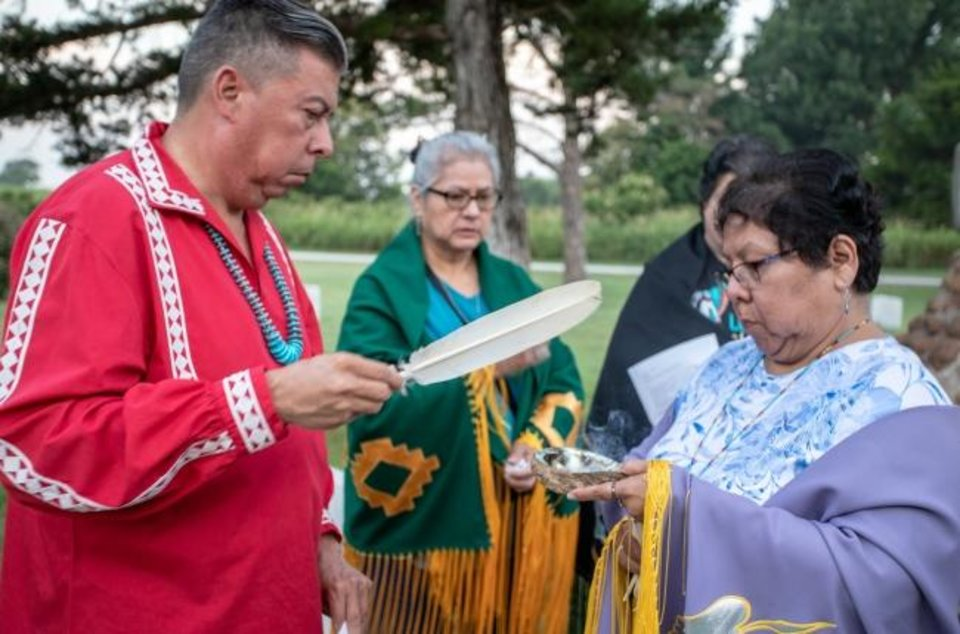 Photo -  The Rev. David Wilson, superintendent of the Oklahoma Indian Missionary Conference, and the Rev. Donna Pewo, with Clinton United Methodist Church and Community Center, participate in a prayer vigil in an Apache POW cemetery at Fort Sill in Lawton. [Ginny Underwood/Oklahoma Indian Missionary Conference]