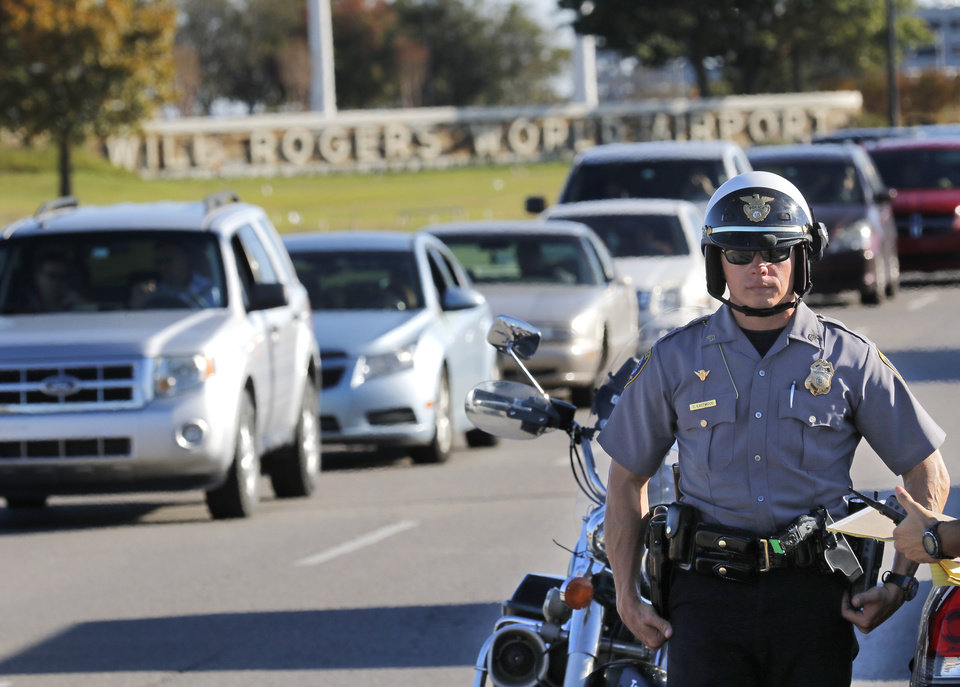 Photo -  An Oklahoma City police officer stops vehicles from leaving Will Rogers World Airport on Nov. 15. The airport was put on lockdown after a fatal shooting. [Photo by Steve Gooch, The Oklahoman Archives]
