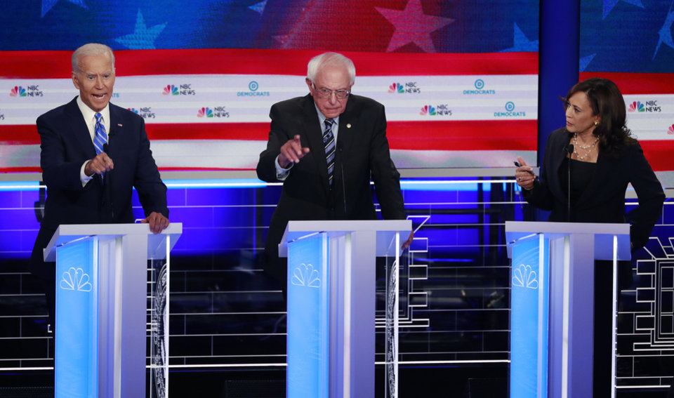 Photo -  Democratic presidential candidate former vice president Joe Biden, left, Sen. Bernie Sanders, I-Vt., and Sen. Kamala Harris, D-Calif., all talk at the same time during the Democratic primary debate hosted by NBC News at the Adrienne Arsht Center for the Performing Arts, Thursday, June 27, 2019, in Miami. [AP Photo/Wilfredo Lee]