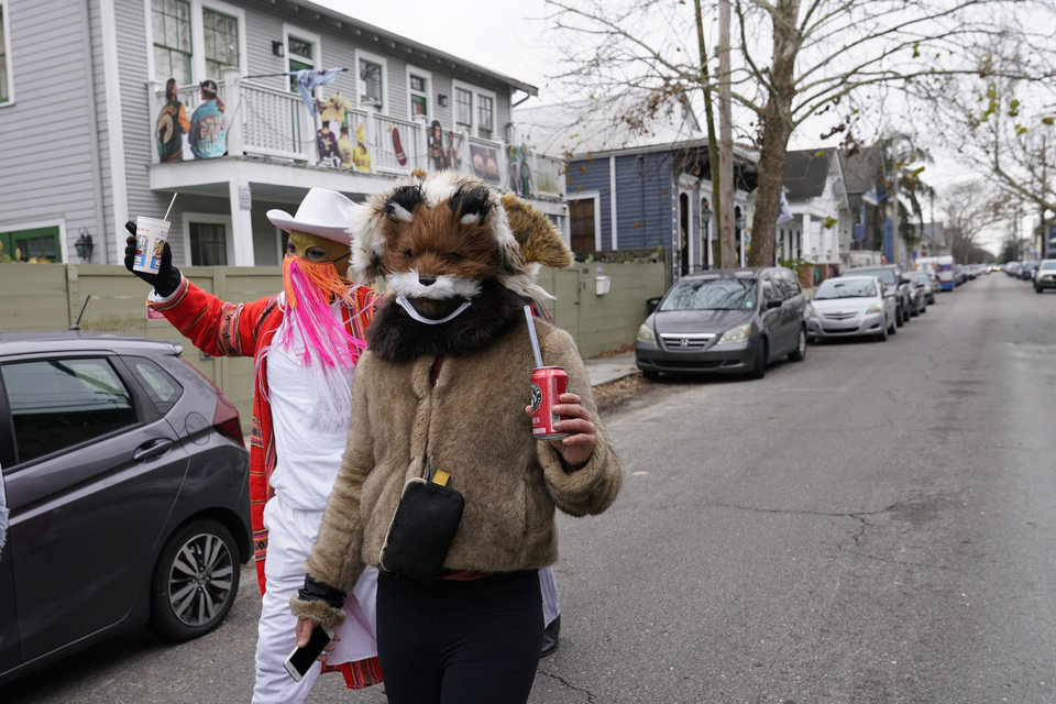 Photo -  Revelers dressed in costumes walk past decorated homes on Mardi Gras Day in the Bywater section of New Orleans, Tuesday, Feb. 16, 2021. Mardi Gras has arrived in New Orleans. But between cold weather and COVID-19, morning streets were nearly empty rather than jam-packed with picnickers and parade watchers. (AP Photo/Gerald Herbert)