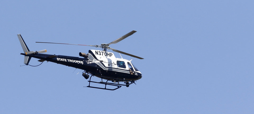 Photo - OHP helicopter aids in the search for the suspect in shooting death of deputy. The man accused of fatally shooting a Logan County sheriff's deputy Tuesday, April 18, 2017,  and leading authorities on a manhunt near Langston, is in custody, according to Logan County Sheriff Damon Devereaux.  Authorities identified Nathan Aaron LeForce, 45, as the person who shot Logan County Sheriff's Deputy David Wade while Wade was serving an eviction notice at a home in Mulhall.     Photo by Jim Beckel, The Oklahoman