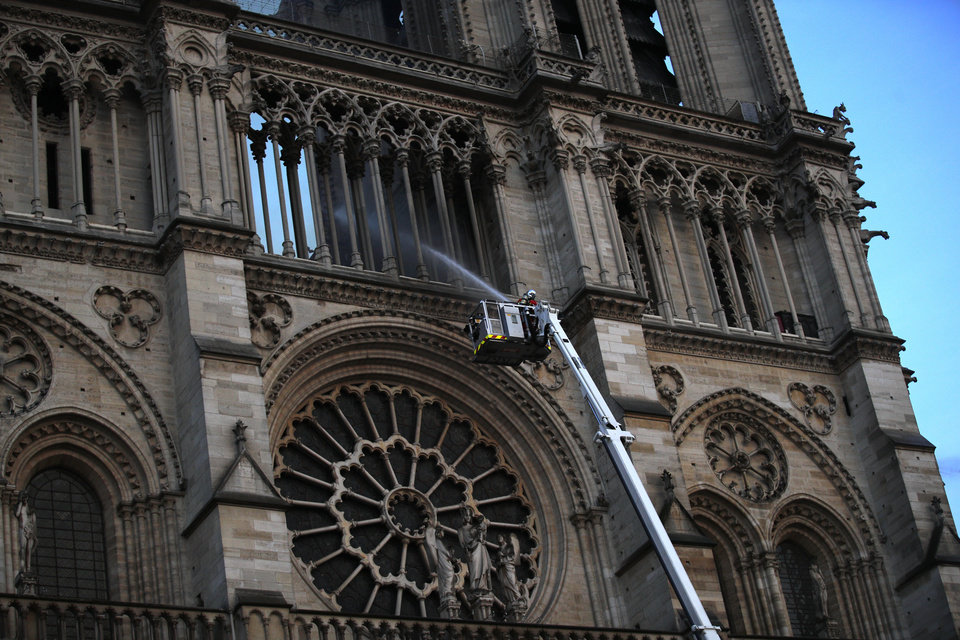 Photo - A fire fighter sprays a liquid into Notre Dame cathedral while the monument is burning in Paris, Monday, April 15, 2019. A catastrophic fire engulfed the upper reaches of Paris' soaring Notre Dame Cathedral as it was undergoing renovations Monday, threatening one of the greatest architectural treasures of the Western world as tourists and Parisians looked on aghast from the streets below. (AP Photo/Francois Mori)