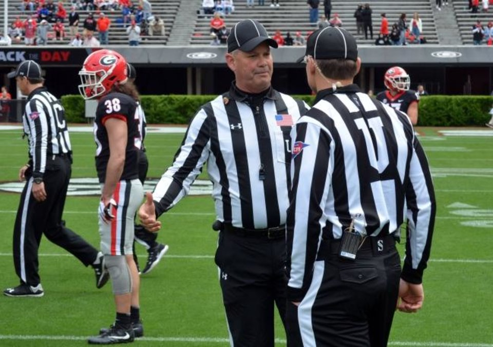 Photo -  Tom Quick talks with a colleague during Georgia's spring game April 20 in Athens, Ga. College referee's jobs have never been more difficult. Those who do it face relentless, often uninformed criticism, and attacks on their credibility. [Gary McGriff via AP]