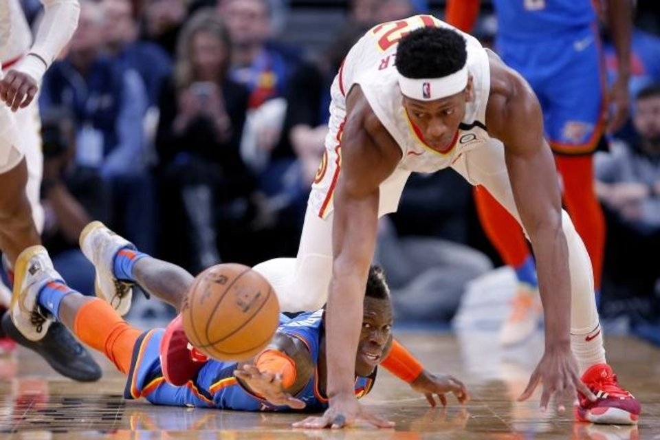Photo -  Oklahoma City's Dennis Schroder (17) tries to get a loose ball from Atlanta's De'Andre Hunter (12) during the Thunder's 140-111 win Friday night. [Sarah Phipps/The Oklahoman]