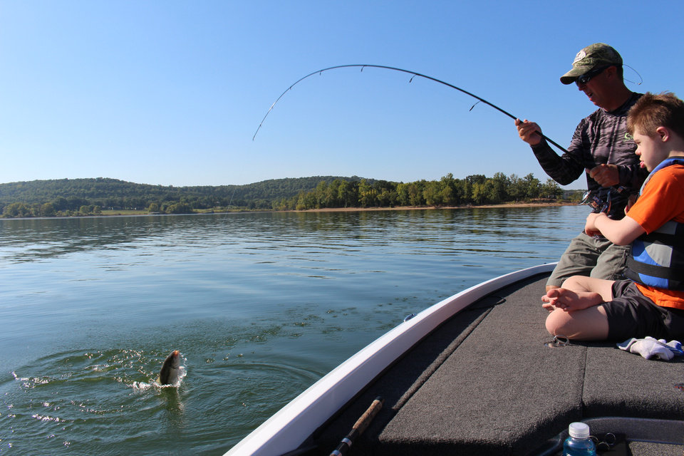 Photo -  Cade Godfrey, 13, of Edmond, catches a bass on Missouri's Table Rock Lake with the help of fishing guide Tony Weldele of Rainbow Chasers Guide Service. [PHOTO BY LINDA LYNN, THE OKLAHOMAN]