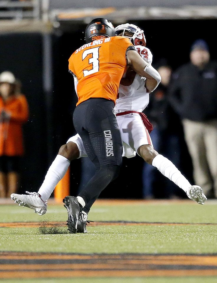 Photo - Oklahoma State's Tre Sterling (3) tackles Oklahoma's Charleston Rambo (14) in the third quarter during the Bedlam college football game between the Oklahoma State Cowboys (OSU) and Oklahoma Sooners (OU) at Boone Pickens Stadium in Stillwater, Okla., Saturday, Nov. 30, 2019. OU won  34-16. Sterling was called for targeting. [Sarah Phipps/The Oklahoman]