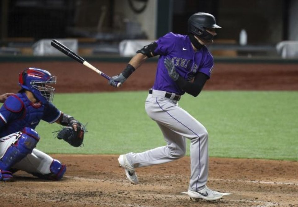 Photo -  Colorado Rockies Sam Hilliard gets a hit in the fifth inning against the Texas Rangers in an exhibition game Tuesday. [AP Photo/Richard W. Rodriguez]