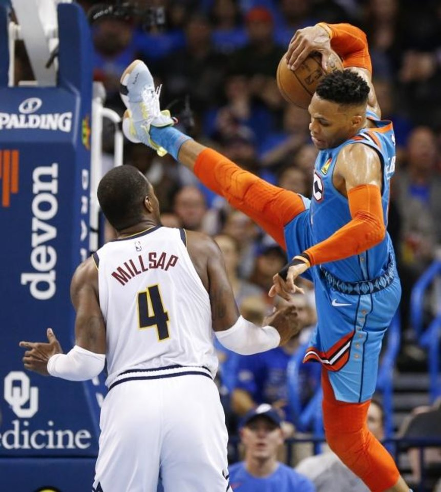 Photo -  Oklahoma City's Russell Westbrook (0) falls to the court after being fouled by Denver's Paul Millsap (4) in the fourth quarter of the Nuggets' 115-105 win Friday at Chesapeake Energy Arena. [Nate Billings/The Oklahoman]