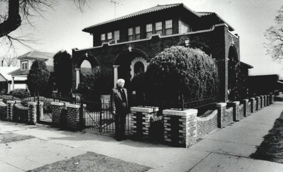 Photo -  Melvin Luster, shown in front of his home at 300 NE 3, visited with The Oklahoman in 1983 about his efforts to fight for survival of his neighborhood amidst rising crime, construction of a nearby highway and Urban Renewal acquisition efforts. The Urban Renewal Authority is now set to buy and preserve the property, including the shotgun house shown to the left of the mansion. [OKLAHOMAN ARCHIVES]