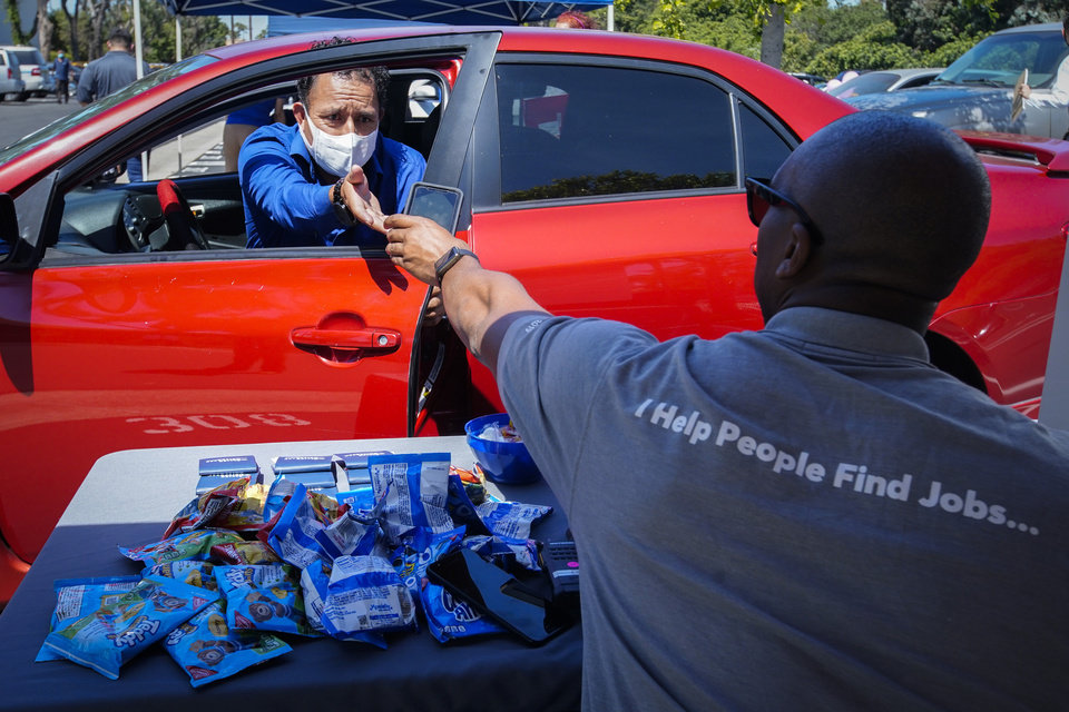 Photo -  FILE - In this May 6, 2020, file photo, Brandon Earl, right, helps David Lenus, a job seeker, fill out an application at a drive up job fair for Allied Universal during the coronavirus pandemic, in Gardena, Calif. Coronavirus restrictions in California have put millions of people out of work, increasing the state's unemployment rate earlier this year to levels not seen since the Great Depression. (AP Photo/Chris Carlson, File)