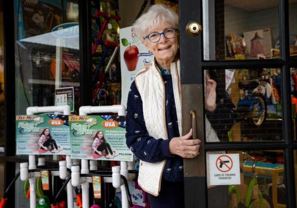 Photo -  Patti Tepper-Rasmussen, owner of Learning Tree Toys, Books and Games, poses for a photo with her front door sign that lets patrons know guns are not permitted inside the store. [Chris Landsberger/The Oklahoman]