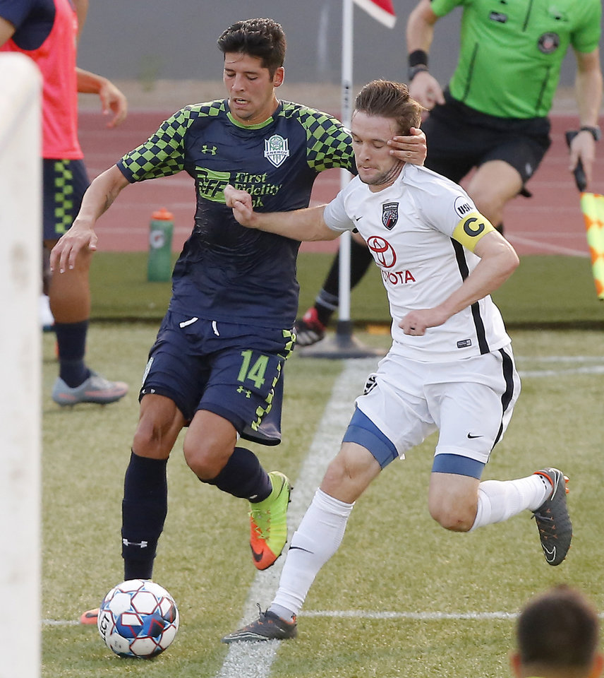 Photo -  Energy FC's Jose Barril, left, chases down the ball beside San Antonio FC's Greg Cochrane on Saturday during San Antonio's 2-1 win at Taft Stadium. [Photo by Bryan Terry, The Oklahoman]