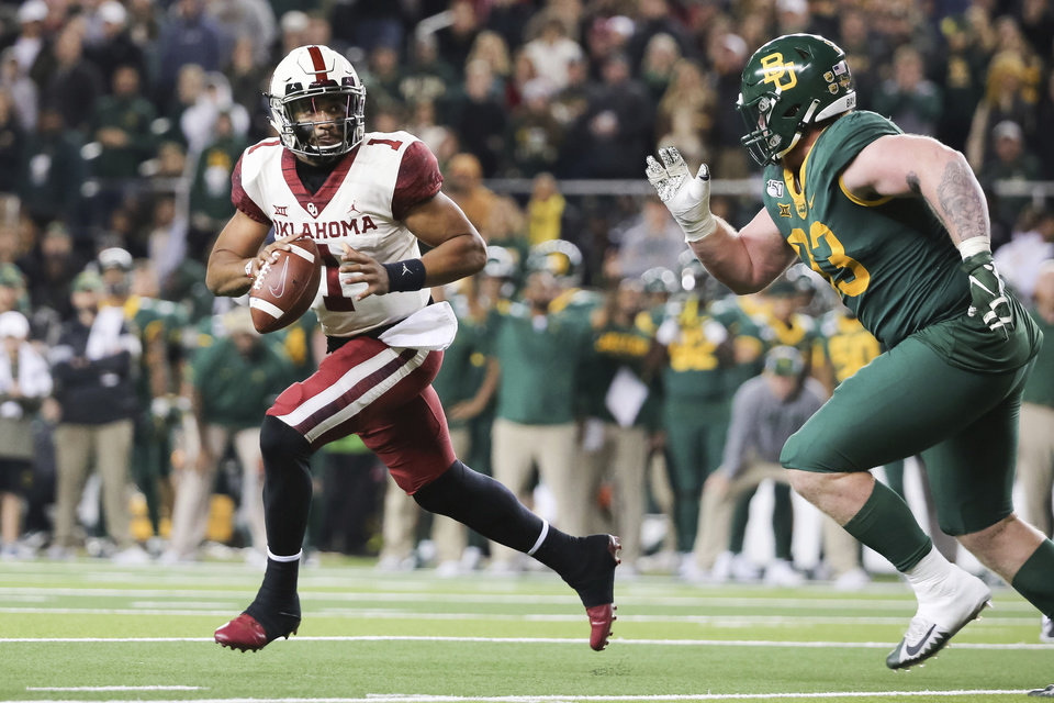 Photo - Oklahoma quarterback Jalen Hurts, left, rolls away from the pressure by Baylor defensive tackle James Lynch, right, during an NCAA college football game in Waco, Texas, Saturday, Nov. 16, 2019. Oklahoma won 34-31. (AP Photo/Ray Carlin)