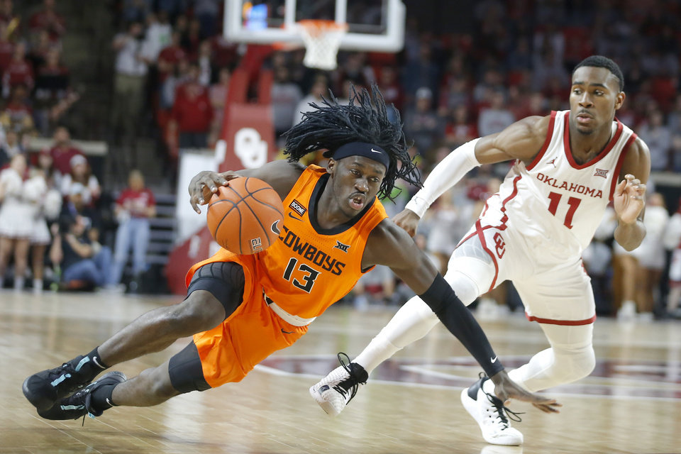 Photo - Oklahoma State's Isaac Likekele (13) falls as he goes past Oklahoma's De'Vion Harmon (11) during a Bedlam college basketball game between the University Oklahoma Sooners (OU) and the Oklahoma State Cowboys (OSU) at the Lloyd Noble Center in Norman, Okla., Saturday, Feb. 1, 2020. [Bryan Terry/The Oklahoman]