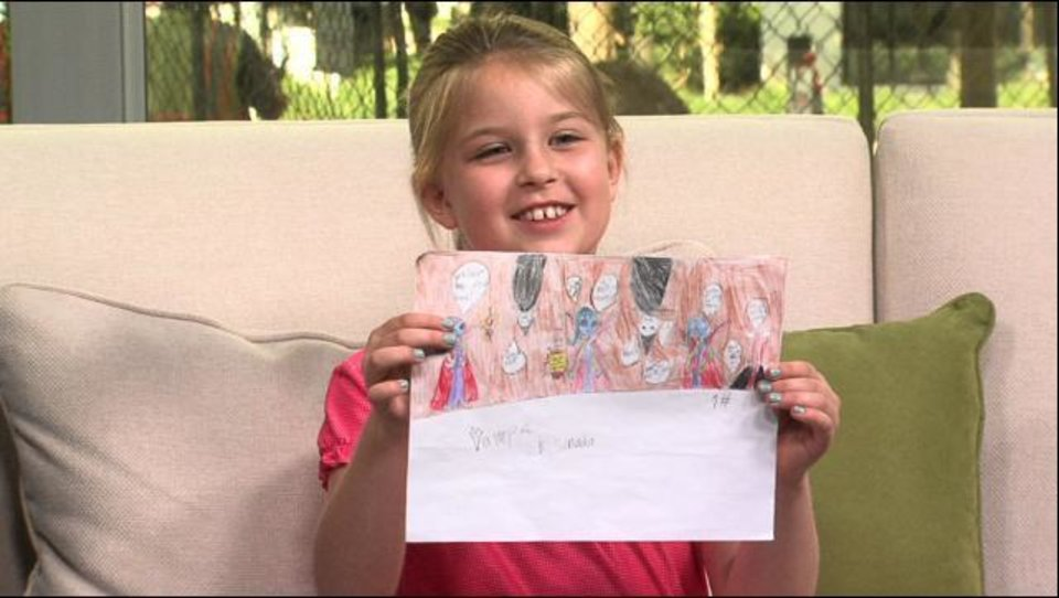 Photo -  Abigail Stemmons holds the comic strip she created during a video at The Oklahoman. Screenshot from video.