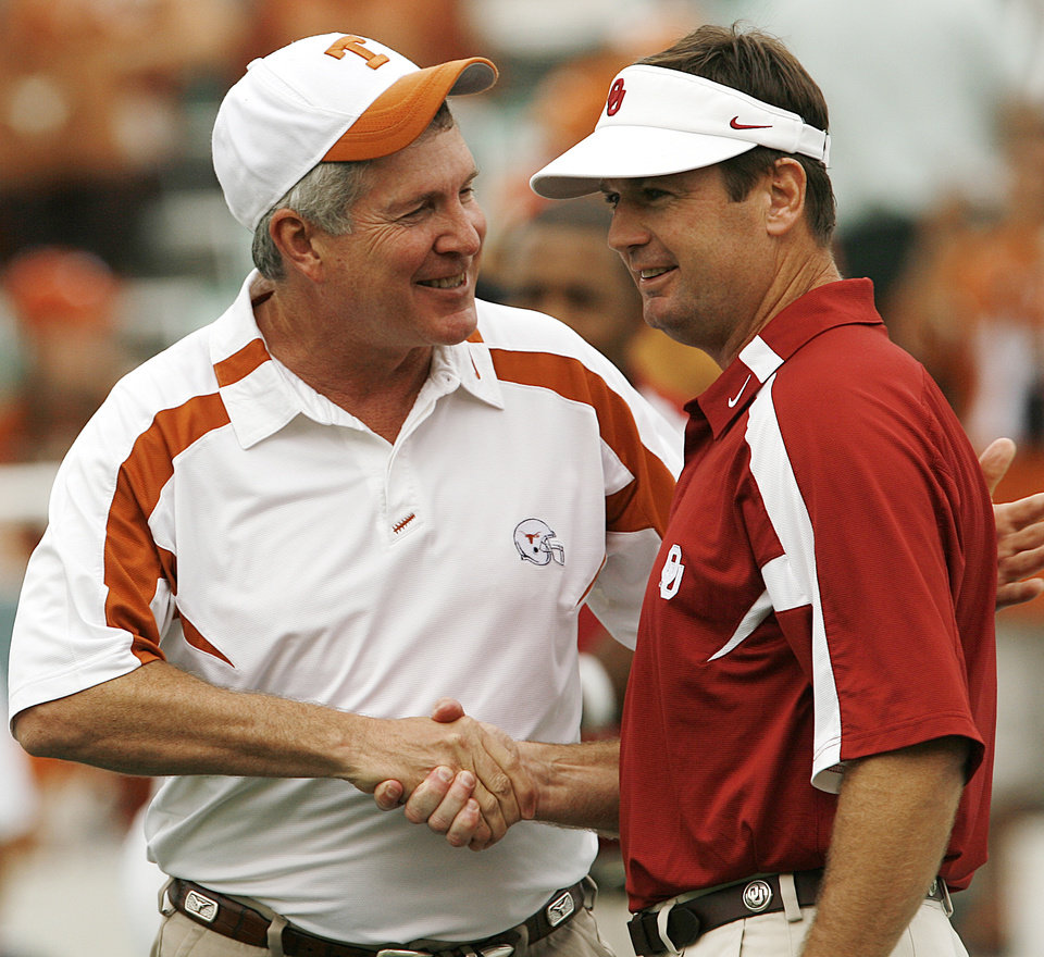 Photo - Texas coach Mack Brown and Oklahoma coach Bob Stoops shake hands before the college football game between the University of Oklahoma Sooners (OU) and the University of Texas Longhorns (UT) at the Cotton Bowl on Saturday, Oct. 6, 2007, in Dallas, Texas.  By Steve Sisney, The Oklahoman  ORG XMIT: KOD
