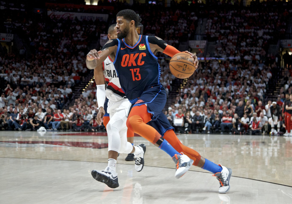 Photo - Oklahoma City Thunder forward Paul George, foreground, drives to the basket past Portland Trail Blazers guard Rodney Hood during the first half of Game 5 of an NBA basketball first-round playoff series, Tuesday, April 23, 2019, in Portland, Ore. (AP Photo/Craig Mitchelldyer)