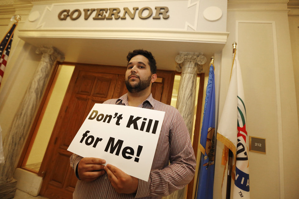 Photo - Hossein Dabiri with Oklahoma Coalition Against the Death Penalty holds a sign protesting the death penalty at the State Capitol in Oklahoma City, Tuesday April 29, 2014. Photo By Steve Gooch, The Oklahoman
