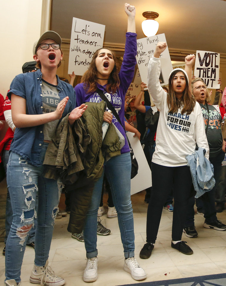 Photo - From left, Paige Clark, 17, Kieron Kessler, 18, and Rebecca Yanez, 18, chant as teachers and protesters for increased education funding rally in front of the entrance to the Senate chamber on the fourth floor during the second day of a walkout by Oklahoma teachers at the state Capitol in Oklahoma City, Tuesday, April 3, 2018. Clark and Kessler are seniors at Moore High School. Yanez is a senior at Norman North. Photo by Nate Billings, The Oklahoman