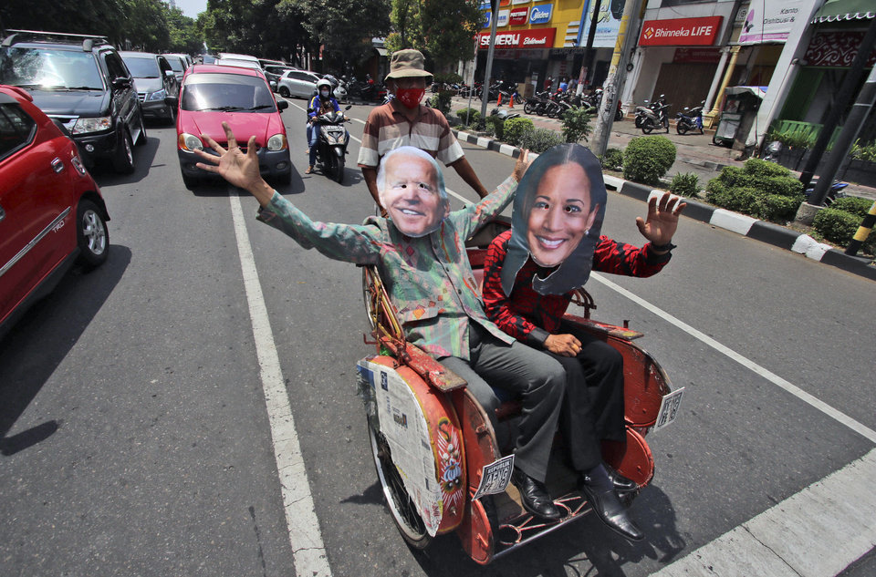Photo -  Indonesian men wearing masks of President-elect Joe Biden and Vice President-elect Kamala Harris wave as they sit on a tricycle as they celebrate their win in the U.S. presidential election, in Solo, Centra Java, Indonesia, , Sunday, Nov. 8, 2020. (AP Photo)