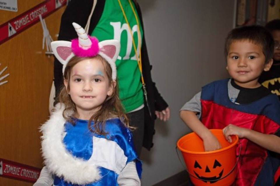 Photo -  Children from Positive Tomorrows are dressed as a unicorn and Spiderman as they trick or treat at Oklahoma Medical Research Foundation. [PROVIDED]