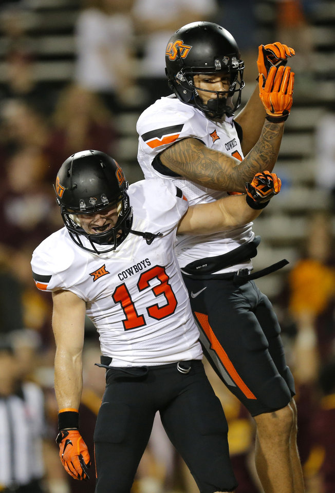 Photo - Oklahoma State's Marcell Ateman (3) and David Glidden (13) celebrates a Ateman touchdown in the fourth quarter  during the college football game between the Central Michigan Chippewas and the Oklahoma State University Cowboys at the Kelly-Shorts Stadium in Mount Pleasant, Mich., Thursday, Sept. 3, 2015. Photo by Sarah Phipps, The Oklahoman