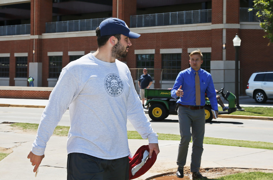 Photo -  Oklahoma quarterback Baker Mayfield declines to answer a reporter's question as he leaves a team meeting where OU coach Bob Stoops announced he is retiring. [AP Photo]