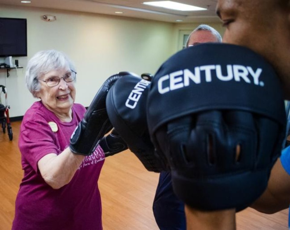 Photo -  Ramona Duff works out with instructor Chris Coleman during a boxing class at Concordia Life Care Community in Oklahoma City.  [Chris Landsberger/The Oklahoman]