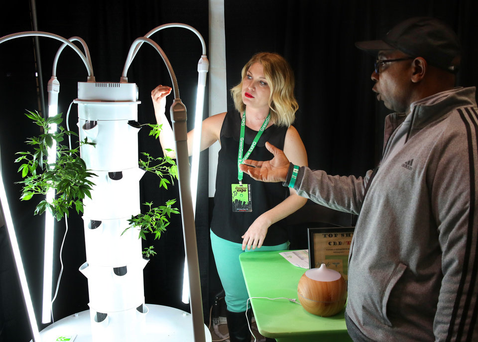 Photo - Amber Walker, owner of Whole Health Oklahoma, LLC, talks about the Tower Garden with Anthony Fletcher at the Green Grow Expo at State Fair Park, Saturday, March 2, 2019.  Photo by Doug Hoke, The Oklahoman
