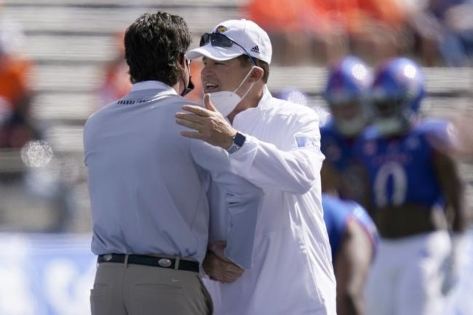 Photo -  Oklahoma State head coach Mike Gundy, left, and Kansas head coach Les Miles talk before an NCAA college football game in Lawrence, Kan., Saturday, Oct. 3, 2020. (AP Photo/Orlin Wagner)