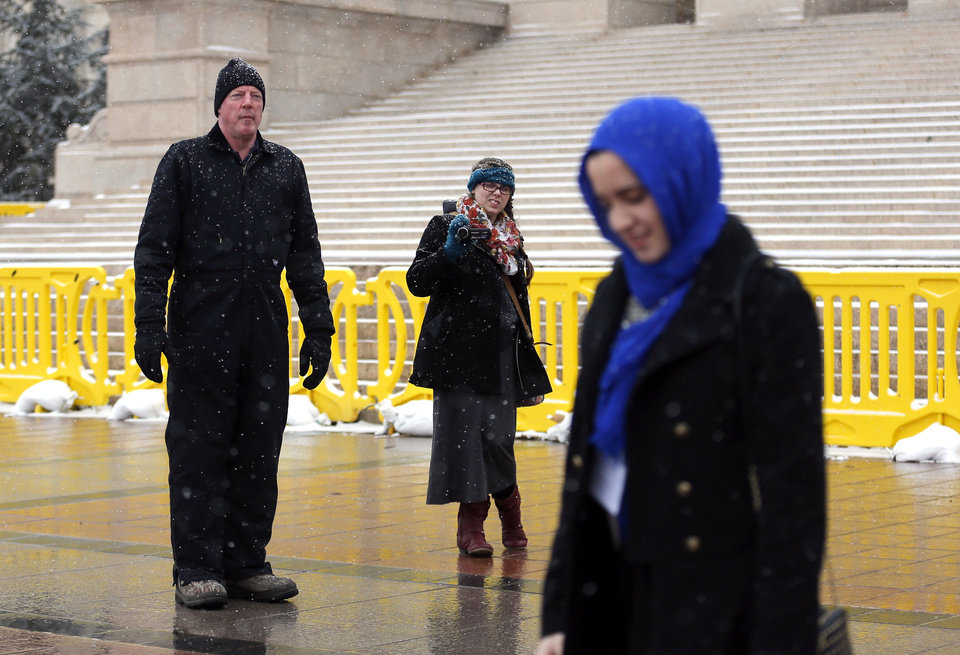 Photo - Guests leave the Oklahoma Muslim Day at the state Capitol as a protestor shouts in Oklahoma City Friday, Feb. 27, 2015. Photo by Sarah Phipps, The Oklahoman