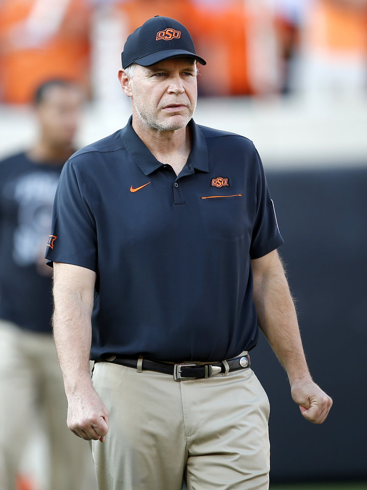 Photo - OSU's Jim Knowles, Defensive Coordinator / Linebackers, watches players stretch before the college football game between the Oklahoma State Cowboys and the Kansas State Wildcats at Boone Pickens Stadium in Stillwater, Okla., Friday, Sept. 27, 2019. [Sarah Phipps/The Oklahoman]