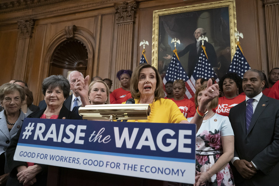 Photo -  Speaker of the House Nancy Pelosi, D-Calif., joins fellow Democrats and activists seeking better pay as the House approved legislation to raise the federal minimum wage for the first time in a decade to $15 an hour, at the Capitol in Washington, Thursday, July 18, 2019. The bill is expected to fail in the Republican-controlled Senate. [AP Photo/J. Scott Applewhite]