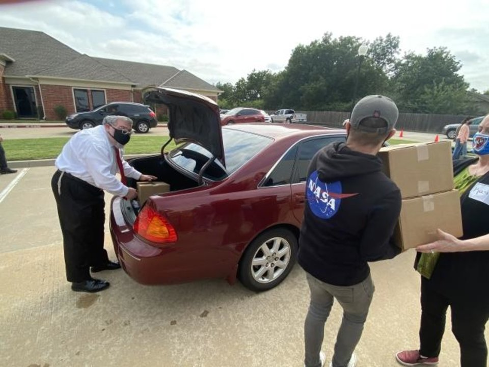 Photo -  Rabbi Ovadia Goldman places a box of food into a car during a food distribution event on Sept. 10 at Chabad Community Center for Jewish Life and Learning, 3000 W Hefner Road. [Photo provided]