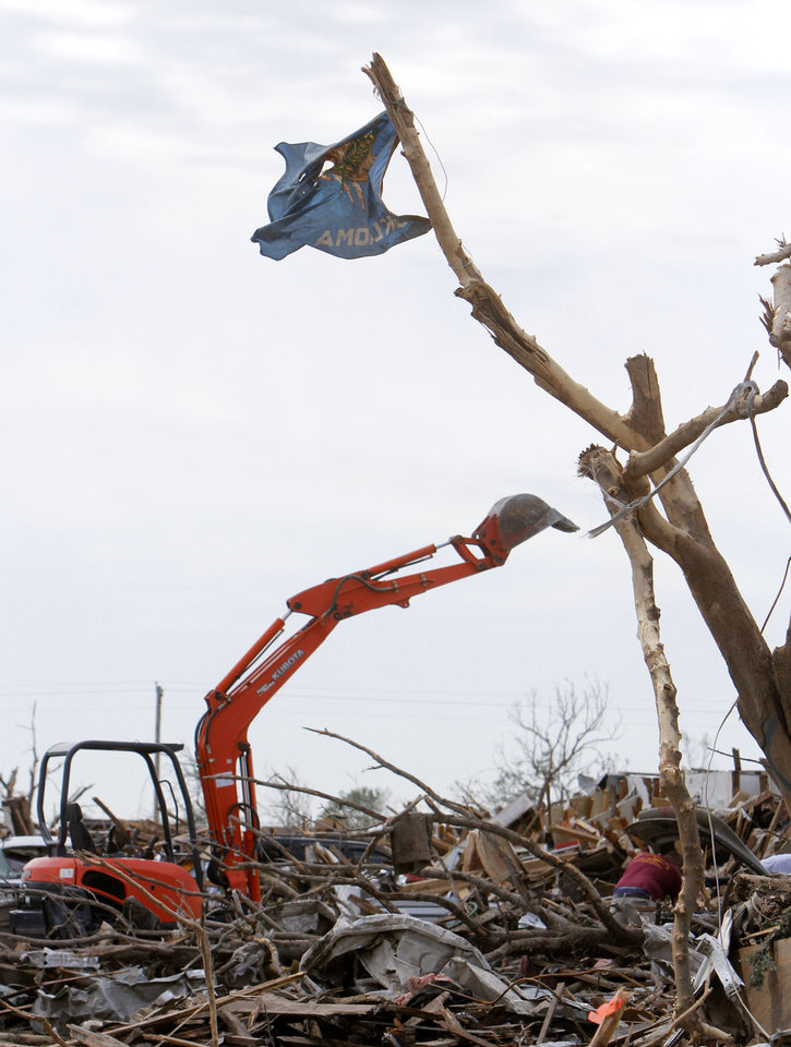 Photo - An Oklahoma flag hangs from a tree in the tornado devastated part of Moore, OK, Thursday, May 23, 2013,  Photo by Paul Hellstern, The Oklahoman