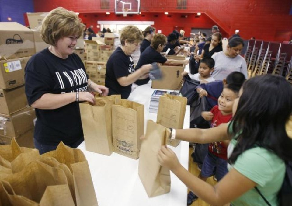 Photo -  OKC Faith Church vlunteer Robin Totten hands bags of school supplies to children at the 2009 Feeding the 5,000 and More back-to-school event at the church, 800 S Portland. [The Oklahoman Archives]